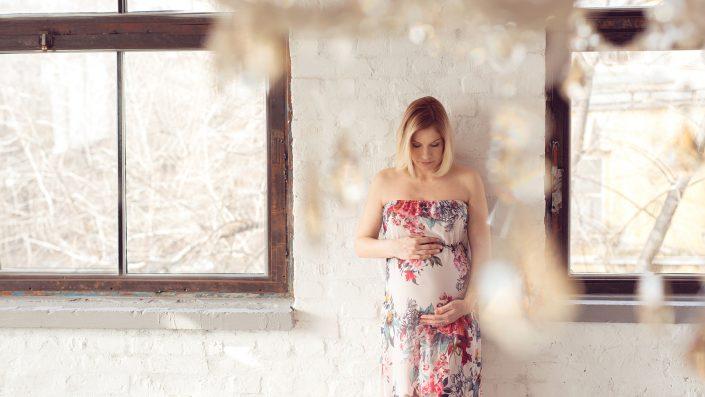 kismama öleli a pocakját virágos ruhában exkluzív stúdióban